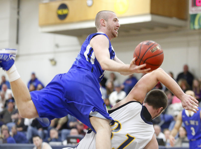 Matt Sullivan of St. Joe's collides with USM's Tyler Penney as he drives to the basket during the Monks' 70-56 win at Hill Gymnasium on Sunday.