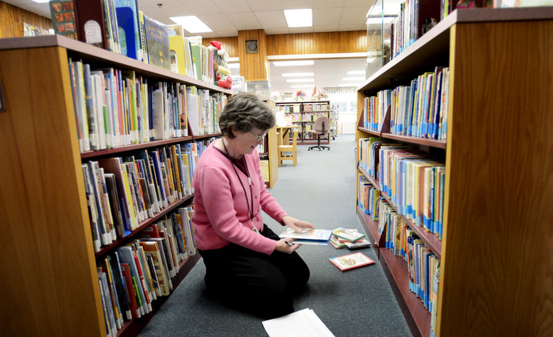Joan Carrier, a library technician at Thomas Memorial Library in Cape Elizabeth, picks out holiday book for display on Monday, Nov. 26, 2012.