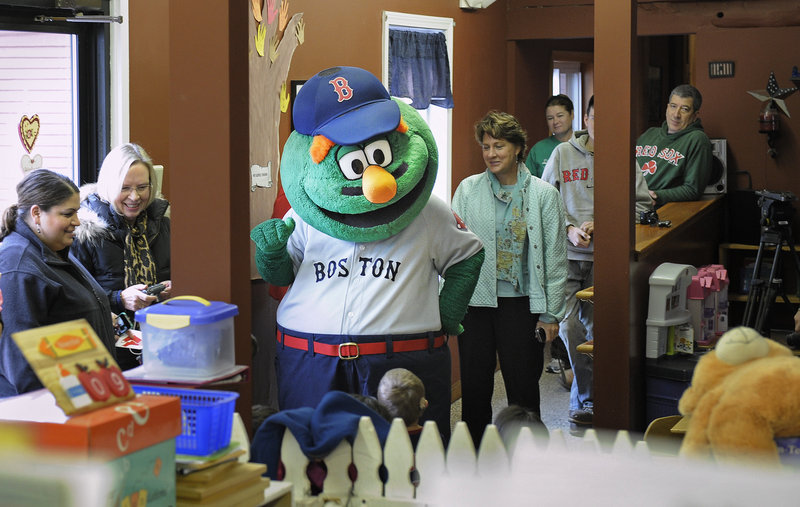 Wally the Green Monster, along with Red Sox players Mark Melancon, Ryan Kalish and Chris Carpenter visit the Briarwood Children's House on Tuesday as part of the team's holiday road trip.