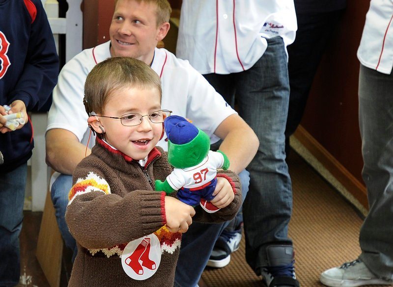 Thomas Morin stares in fascination at his new Wally the Green Monster while Sox pitcher Mark Melancon watches from behind.