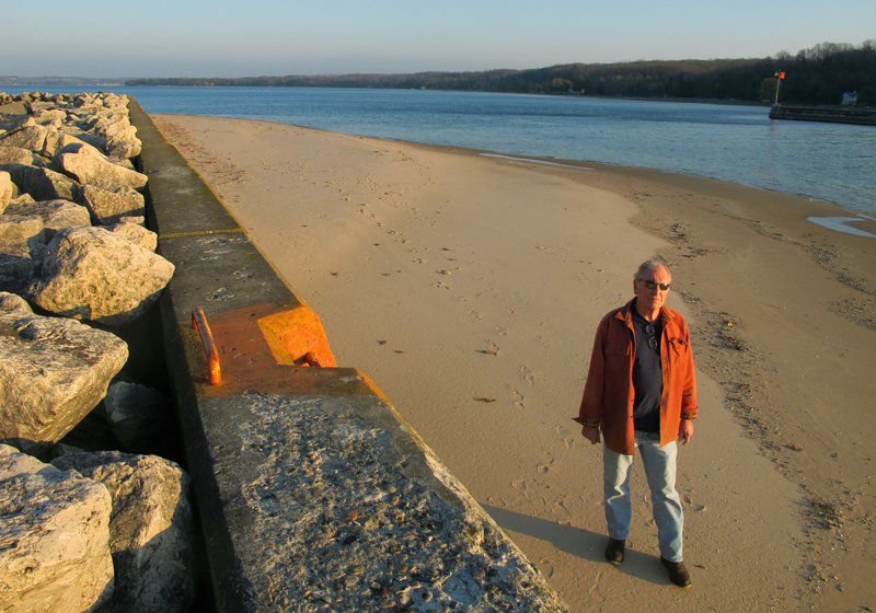Jim Simons, who runs a rod and reel repair business, strolls on a sandbar by the channel leading to Lake Michigan at Onekama, Mich. The bar normally would be submerged, but low water levels have exposed the the bottom in many areas.