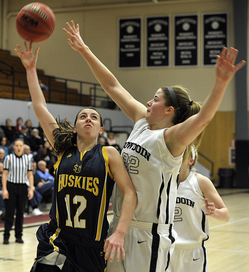 Erin McNamara of the University of Southern Maine, left, finds enough room to lift a shot over Megan Phelps of Bowdoin during their nonconference game Tuesday night, USM pulled away in the second half for a 72-58 victory.