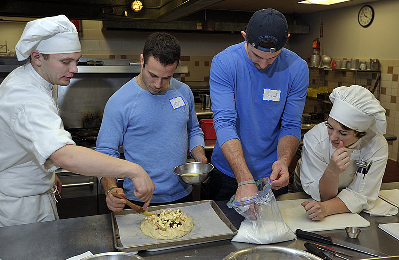 Culinary arts students Dillon Newcombe. left, and Audrey Carlson help Andy Miele and Chris Brown put an egg mixture glaze on the crust for a rustic apple tart they are making Tuesday. Brown said he hopes the cooking class helps him eat more healthy meals.