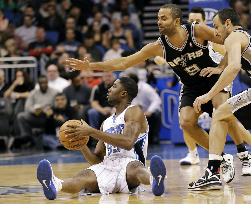 E'Twaun Moore of the Orlando Magic looks to pass Wednesday night after beating Tony Parker, 9, and Manu Ginobili of San Antonio to a loose ball. The Spurs won, 110-89.