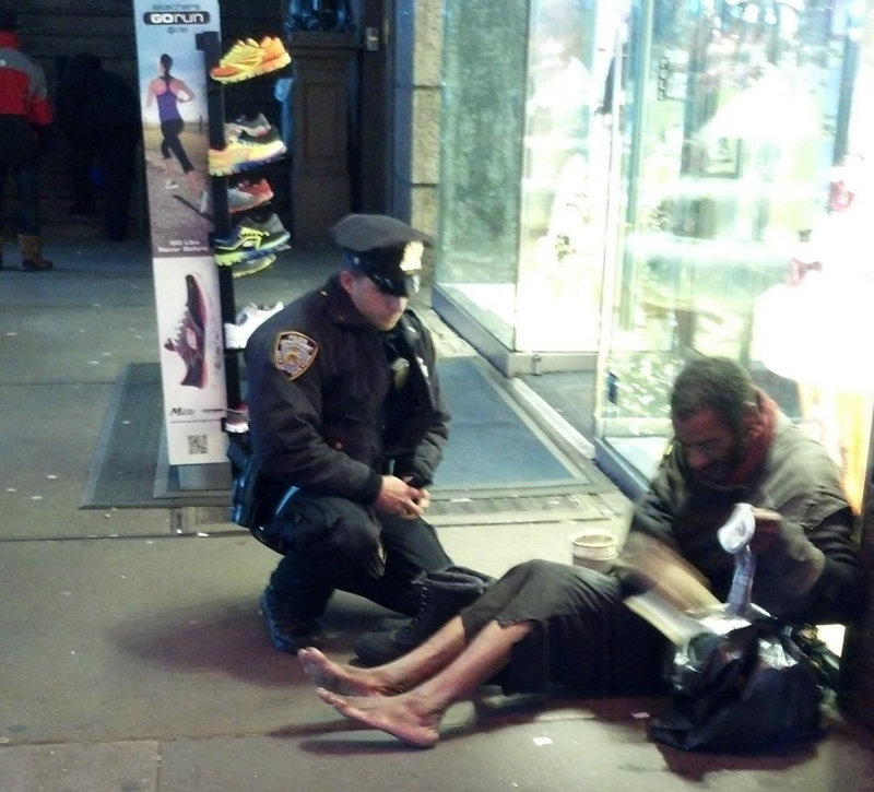 Photo provided by Jennifer Foster of Florence, Ariz., shows New York City Police Officer Larry DePrimo presenting socks and boots to a barefoot homeless man in New York's Time Square on Nov. 14.
