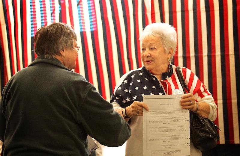 Alice Voisine, right, greets her friend Rita Probost while voting in Skowhegan on Tuesday.