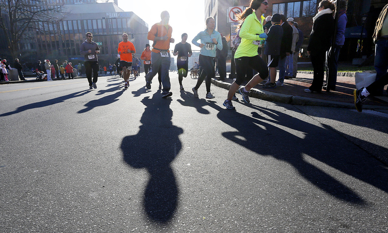 Participants in the Portland Thanksgiving Day 4-miler cast shadows on Temple Street on Thursday morning.