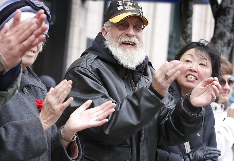 Stephen Betters of Portland and his wife, Sun, right, applaud during the Portland Veterans Day parade on Sunday. Betters served in the U.S. Army from 1973 to 1993.