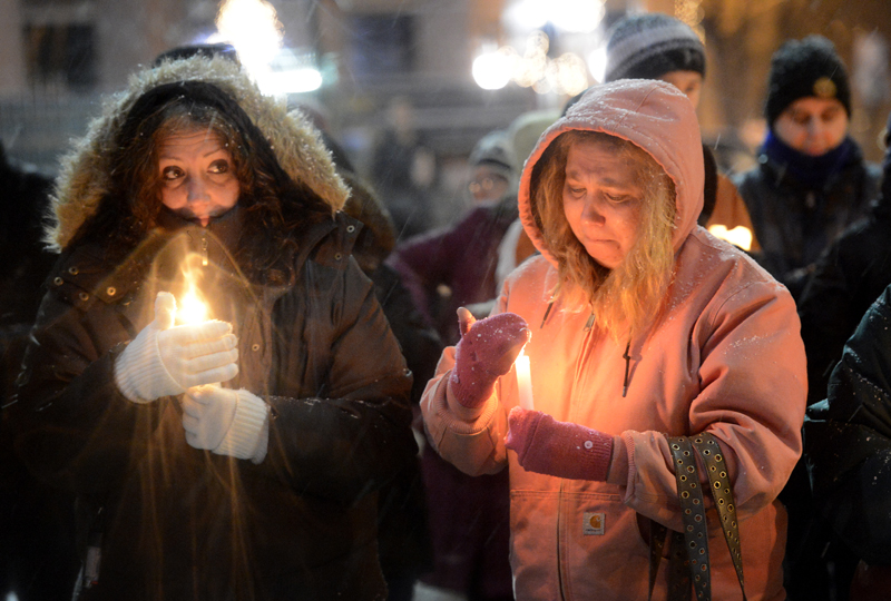 Julie Parker, left, and Alisa Dunham, both of Portland, were among the 200 who attended a vigil Sunday at Monument Square in Portland to support victims of Friday's school shooting in Newtown, Conn.