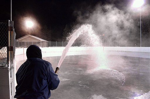 With temperatures in the single digits, city parks and recreation employee Greg Pecha floods a hockey rink Wednesday evening, Dec. 26, 2012 at Roosevelt Park in Eau Claire, Wis. Skating rinks in the city are opening a bit later than usual due to above-average temperatures earlier in the month. (AP Photo/Eau Claire Leader-Telegram, Steve Kinderman).
