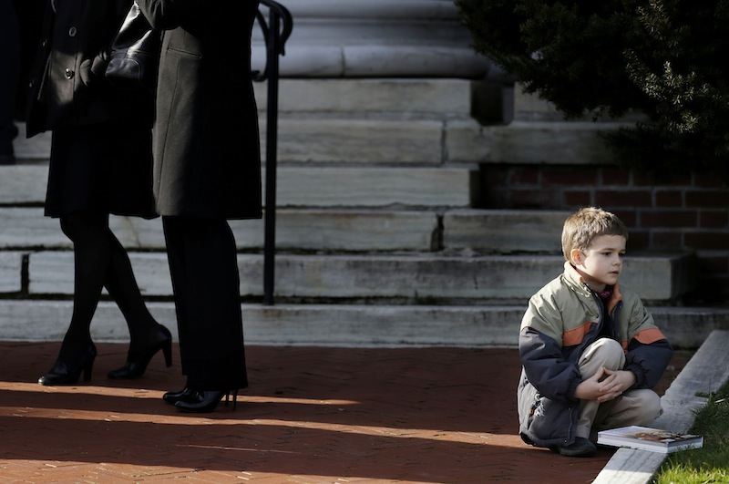 The Associated Press A boy sits outside a church before the memorial service for Lauren Rousseau in Danbury, Conn., on Thursday. Rousseau, 30, was one of the 26 teachers and children shot to death at Sandy Hook Elementary School last Friday.