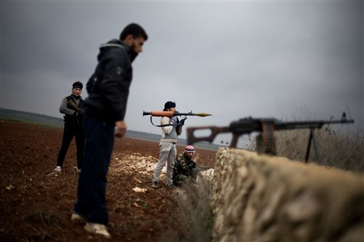 Free Syrian Army fighters take their positions, close to a military base, near Azaz, Syria, on Monday. A State Department report says foreign jihadists have flocked to Syria.