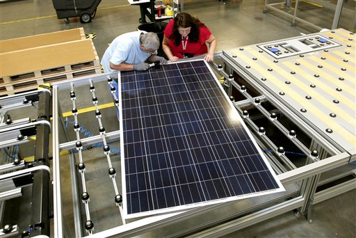 Stacey Rassas, right, a quality control manager at a Suntech Power Holdings Co., a Chinese-owned solar panel manufacturer, examines a solar panel with her co-worker Frank Garcia at a company facility in Goodyear, Ariz., recently. The factory makes solar panels for one of the world's biggest solar manufacturers.