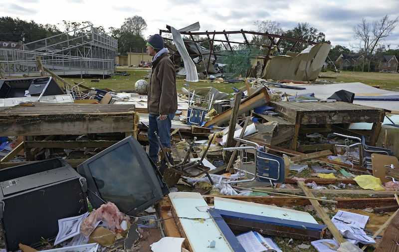 Murphy High School teacher Leland Howard tries to salvage items where his algebra classroom once stood in a temporary building at Murphy High School as residents clean up and assess the damage from a Christmas Day tornado Wednesday, Dec. 26, 2012 in Mobile, Ala. With only a handful of injuries and no deaths reported statewide from the storms, the head of the state's emergency response said it was difficult to fathom how the toll wasn't worse. (AP Photo/G.M. Andrews)
