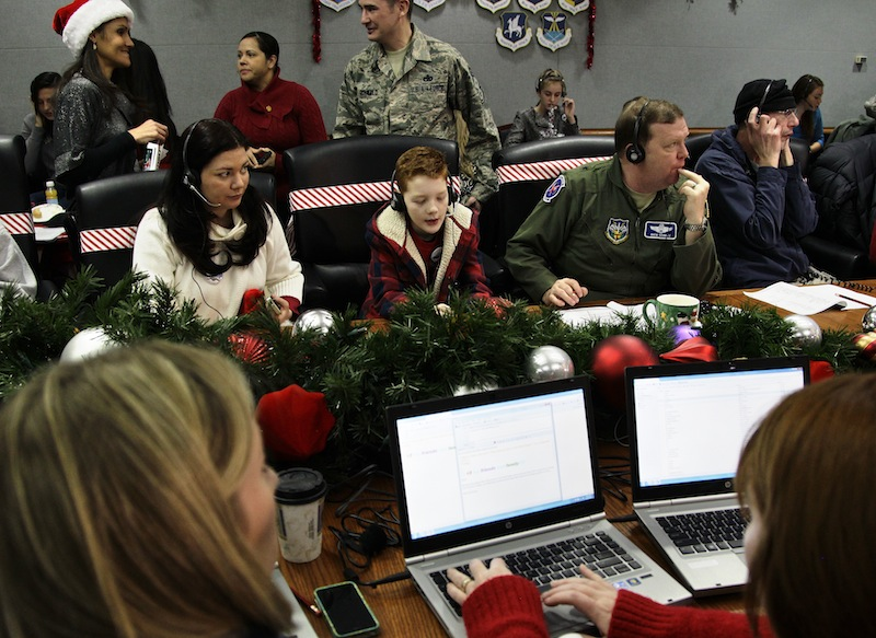 U.S. Air Force Brig. Gen. Richard Scobie, right, flanked by his son Andrew, and wife Janis, all taking phone calls from children asking where Santa is and when he will deliver presents to their house, during the annual NORAD Tracks Santa Operation, at the North American Aerospace Defense Command, or NORAD, at Peterson Air Force Base, in Colorado Springs, Colo., Monday Dec. 24, 2012. Over a thousand volunteers at NORAD handle more than 100,000 thousand phone calls from children around the world every Christmas Eve, with NORAD continually projecting Santa's supposed progress delivering presents. (AP Photo/Brennan Linsley)
