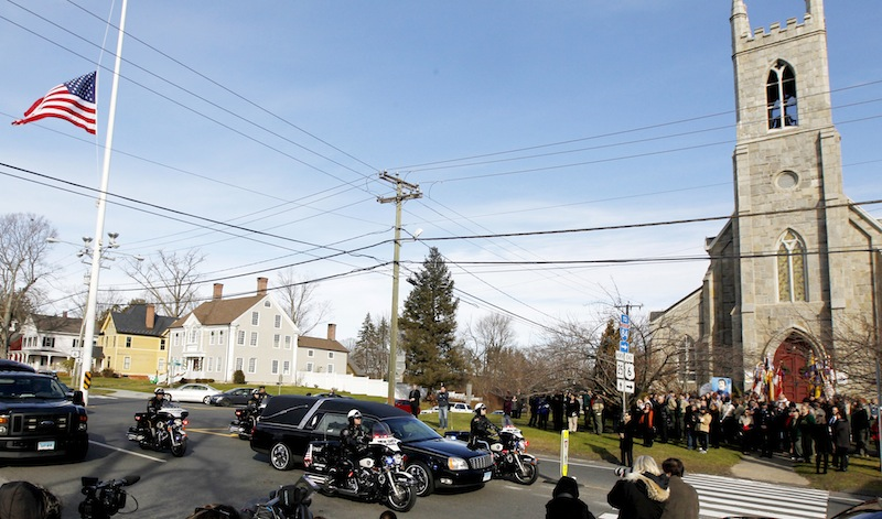 While mourners gather outside of Trinity Episcopal Church on Thursday during funeral services for Benjamin Andrew Wheeler, one of the students killed in the Sandy Hook Elementary School shooting last week, a hearse with another shooting victim passes by.
