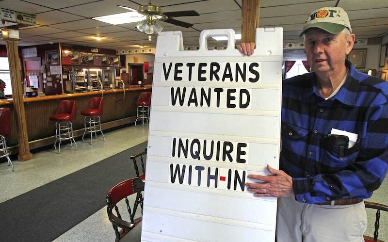 """In this Wednesday, Dec. 19, 2012, Legion Post 3 Commander Dick Harlow poses with a sign in Montpelier, Vt. The American Legion post in Vermont's capital city has a simple method to help attract new members: A sign in the Main Street doorway says """"members wanted."""" They still get new members, sometimes veterans of Iraq and Afghanistan, but few of them are young, most are in their 40s or even older. (AP Photo/Toby Talbot)"""