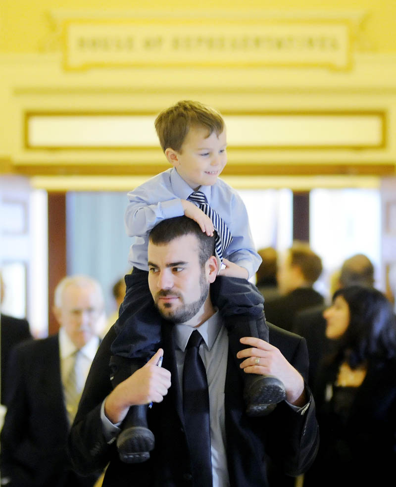Rep. Jeff McCabe, D-Skowhegan, carries his son, Finnegan, 4, Wednesday, before being sworn in for a new term in the House of Representatives at the State House in Augusta.