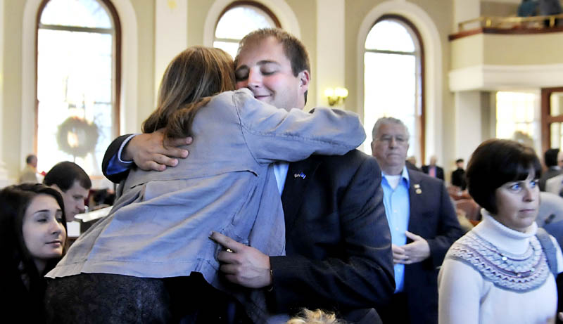 Matt Pouliot, R-Augusta, hugs his mother, Lisa Pouliot, Wednesday before taking the oath of office in the House of Representatives in Augusta.