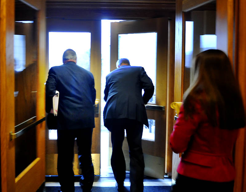 Gov. Paul LePage, left, departs his Augusta office Tuesday with a state police officer and spokesperson Adrian Bennett, right, after declining to speak to the press. Gov. LePage on Tuesday called off his scheduled meeting with incoming Democratic leadership, saying he would not have