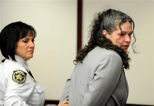 Dee Dee Moore is led into a Hillsborough County courtroom for the reading of the verdict in her murder trial Monday in Tampa, Fla. Moore was convicted Monday of first-degree murder in the slaying of a lottery winner in central Florida.