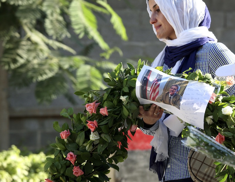 In this Monday, Sept. 17, 2012 file photo, a Libyan woman, Salwa Bugaighis, carries a wreath with a photo of U.S. Ambassador Chris Stevens on it as she and others gather to pay their respect to the victims of the Tuesday, Sept. 11, 2012 attack on the U.S. consulate, in Benghazi, Libya. Stevens and three other Americans were killed in the attack. (AP photo/Mohammad Hannon, File)