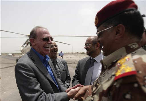 In this June 21, 2012, photo, U.S. Ambassador to Yemen Gerald M. Feierstein shakes hands with a Yemeni army officer during a visit to Abyan, Yemen.