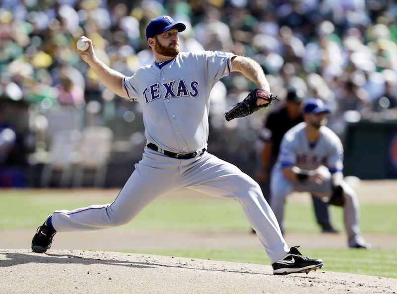 This Oct. 3, 2012 file photo shows Texas Rangers starting pitcher Ryan Dempster throwing against the Oakland Athletics during the first inning of a baseball game in Oakland, Calif. Two people familiar with the negotiations say the Boston Red Sox have agreed to a $26.5 million, two-year contract with Dempster. The people spoke on condition of anonymity Thursday, Dec. 13, 2012, because the agreement is pending a physical. (AP Photo/Marcio Jose Sanchez, File)