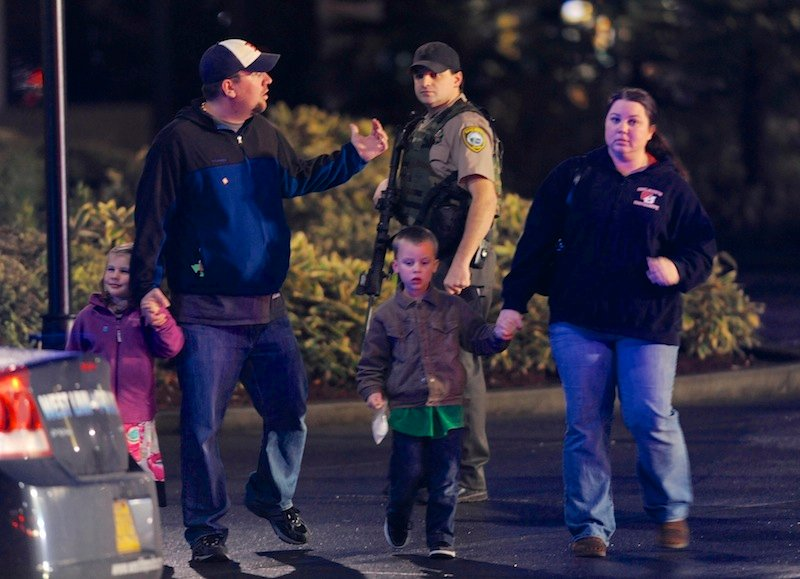A family leaves the scene of a multiple shooting at Clackamas Town Center Mall in Clackamas, Ore., Tuesday. A gunman is dead after opening fire at the mall Tuesday, killing two people and wounding another, sheriff's deputies said.