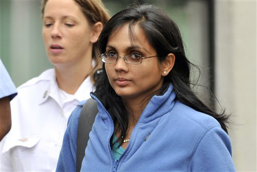 In this Oct. 10, 2012, photo, Annie Dookhan leaves a Boston courthouse escorted by court officers. Dookhan, a Massachusetts chemist is accused of deliberately faking test results on drug samples in criminal cases.