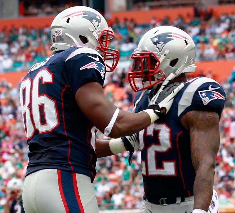 Tight end Daniel Fells, left, congratulates running back Stevan Ridley after Ridley scored a touchdown in the first quarter Sunday against the Dolphins at Miami. The Patriots won, 23-16.