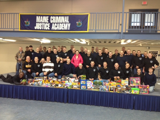 Members of the Maine Criminal Justice Academy's latest graduating class with gifts they gathered to donate to charity.