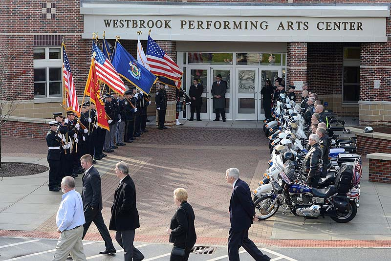 Family and friends of Officer Peter MacVane arrive at his memorial service at the Westbrook Performing Arts Center Sunday.