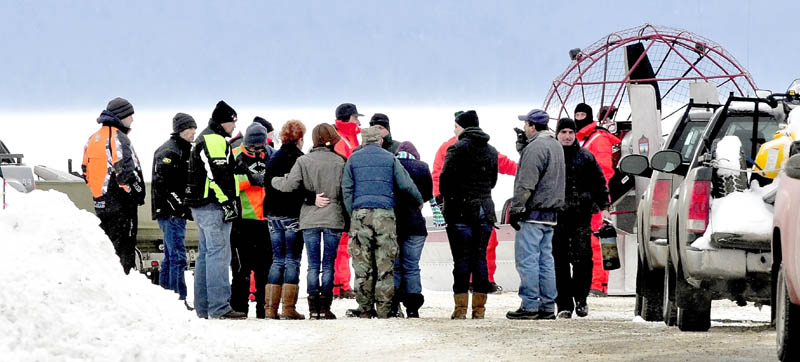 DEADLY ACCIDENT: People seen hugging and holding each other approach Maine Warden Service personnel wearing survival suits at the boat launch on Rangeley Lake on Monday. The body of Dawn Newell was recovered earlier in the day after her snowmobile went through the ice Sunday night.