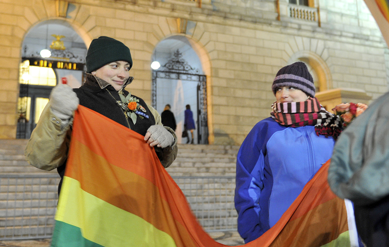 Amber Hardy of Portland and Amanda Poulin of Cape Elizabeth unfurl a gay pride flag in front of Portland City Hall on Friday before the first same-sex marriages were performed.