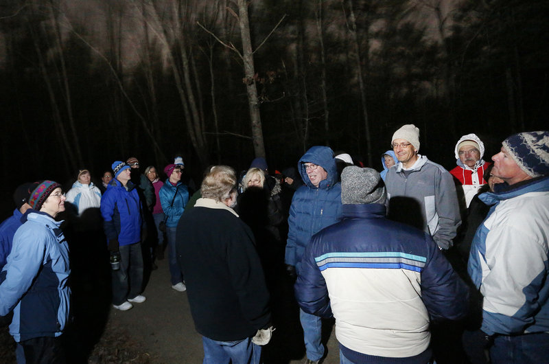 Joe Yuhas (no hat), former University of New England science professor, lectures to more than 40 hikers on the moonlight hike.