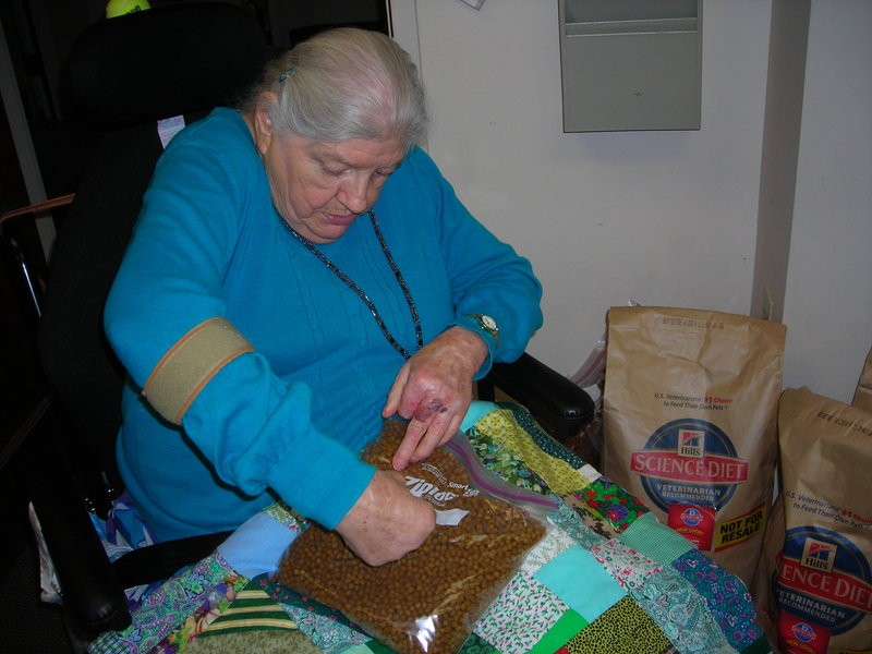 """Dottie Carter helps package pet food that will be delivered, along with regular Meals on Wheels dinners, to seniors who have pets. """"I enjoy my job (volunteering) to help the animals,"""" she said."""