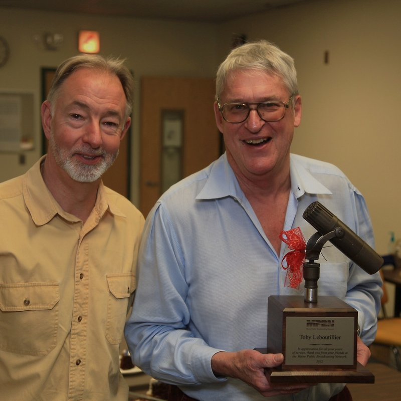 """MPBN program director Charles Beck, left, enjoys a moment with Toby Leboutillier, holding a microphone, after Friday's airing of """"Down Memory Lane."""""""