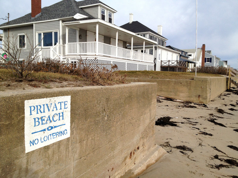 """A sign posted on a seawall at Moody Beach proclaims, """"Private Beach. No Loitering."""" Property owners there won a landmark 1989 case affirming private ownership of the shore straight to the low-water mark. Unlike most other states, Maine's beaches and other intertidal property are not owned by the state, though recent court cases have increased public access rights."""