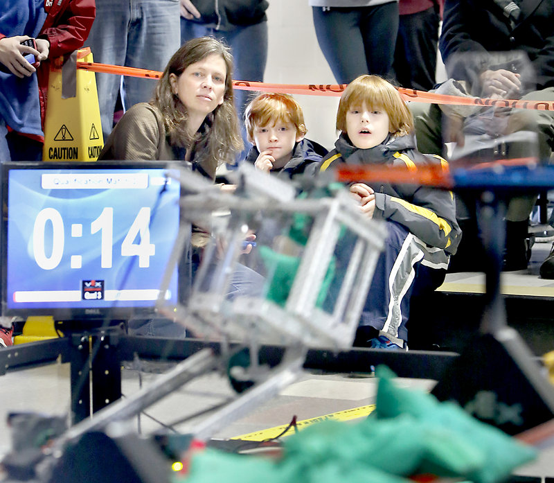 Page Lennig of Scarborough, one of Waynflete School's robotics coaches, and her sons Charlie, 7, middle, and Henry, 9, watch a robot place sacks in a goal Saturday at the VEX Robotics Tournament at Cape Elizabeth Middle School.