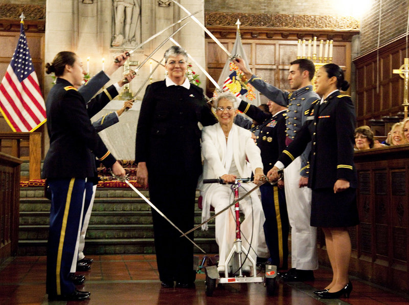 Brenda Sue Fulton, center left, and Penelope Gnesin proceed through an honor guard forming an arch of raised swords after exchanging wedding vows at the U.S. Military Academy at West Point, N.Y., on Saturday.
