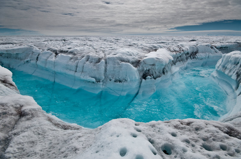 Water from melted ice rushes along the surface of the Greenland ice sheet through a supra-glacial stream channel in this July 4 photo. A new report says heat-trapping pollution from all nations increased by about 1 billion tons last year.