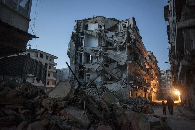 In this Sunday, Dec. 2 photo, residents walk past damaged buildings due to heavy fighting between Free Syrian Army fighters and government forces in Aleppo, Syria.