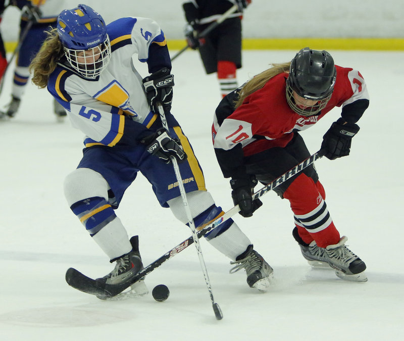 Meg Pierce, left, of Falmouth battles for control of the puck with Scarborough's Rachel Wallace Monday night at Falmouth. Unbeaten Scarborough won 7-0 against the defending Western champions.