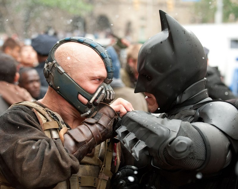 "Tom Hardy as the villainous Bane and Christian Bale as Batman in ""The Dark Knight Rises."""