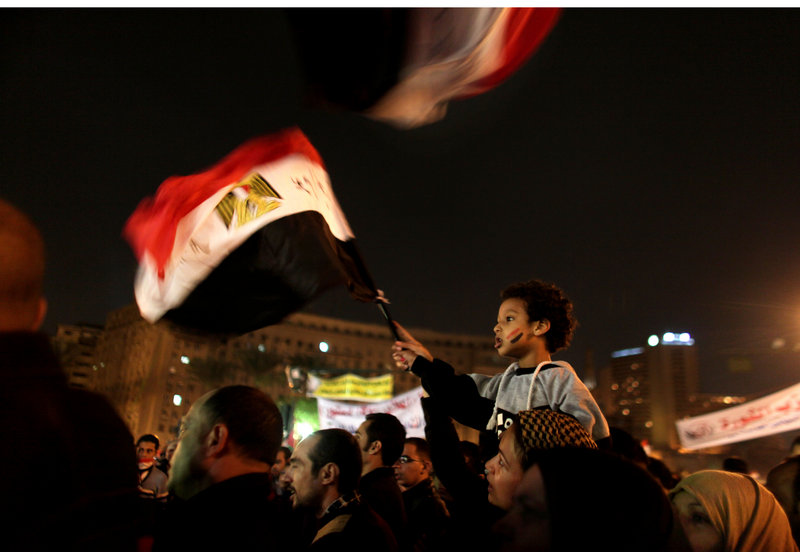 A young Egyptian boy waves a national flag from his mother's shoulders as thousands of protesters gather and chant slogans in Tahrir Square in Cairo on Tuesday.