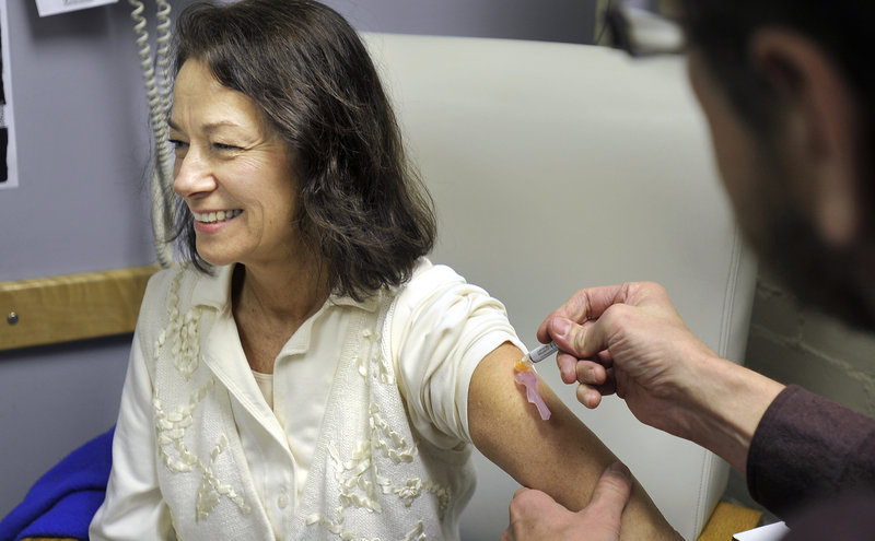 Joanne Yarnold of South Portland receives a flu shot from Bob Barrett, a registered nurse at the India Street Clinic, on Wednesdaym Dec. 5, 2012.