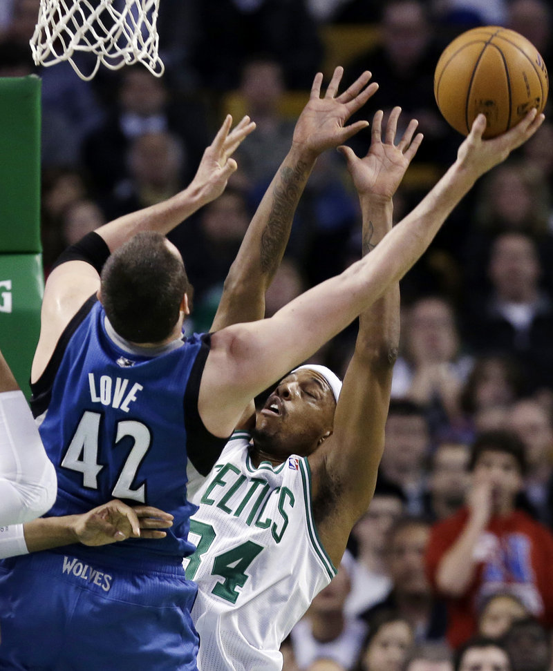 Kevin Love of the Timberwolves shoots while being defended by Paul Pierce of the Celtics Wednesday night in Boston. The Celtics won, 104-94.