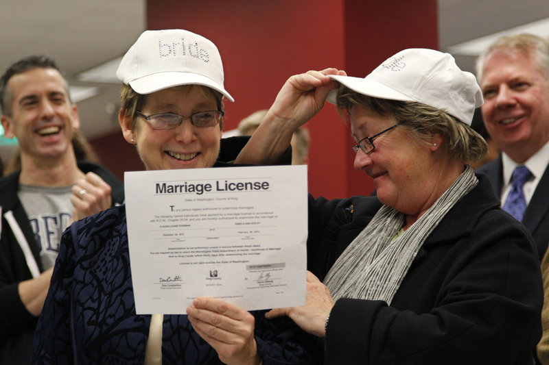 """Claudia Gorbman, left, and partner Pam Keeley both wear caps reading """"bride"""" as they display their marriage license Thursday in Seattle."""