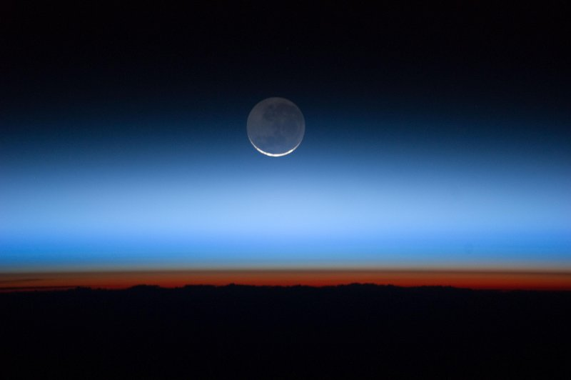 Image from the Expedition 28 crew on the International Space Station shows the moon with the Earth near the bottom transitioning into the troposphere, the lowest and most dense portion of the Earth's atmosphere.